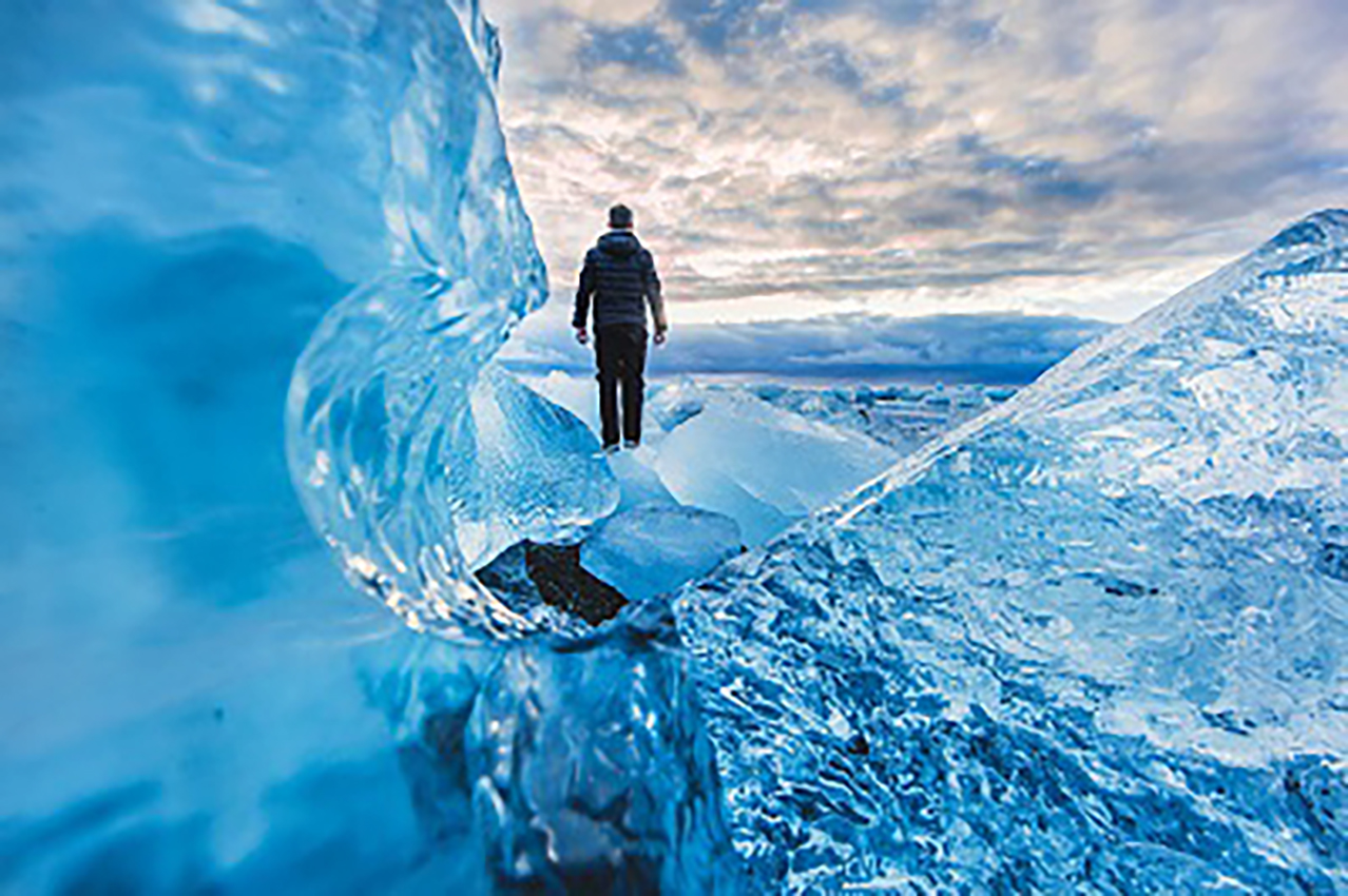 man waking on glacier demonstrating impact of water - link to impact studio