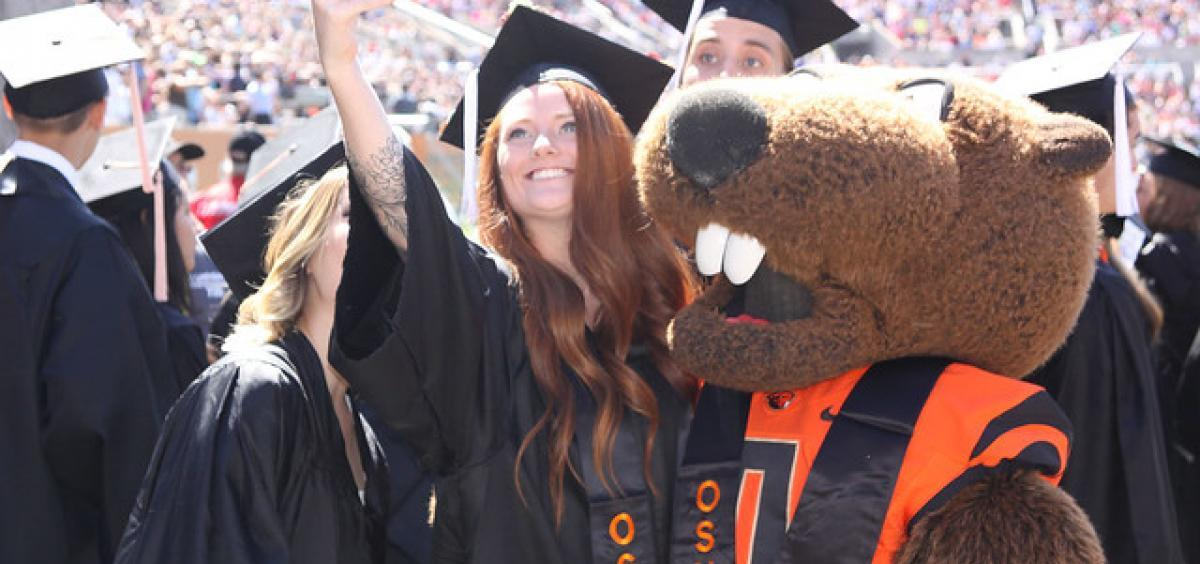 Photo of graduate with Benny Beaver at OSU Commencement 2019